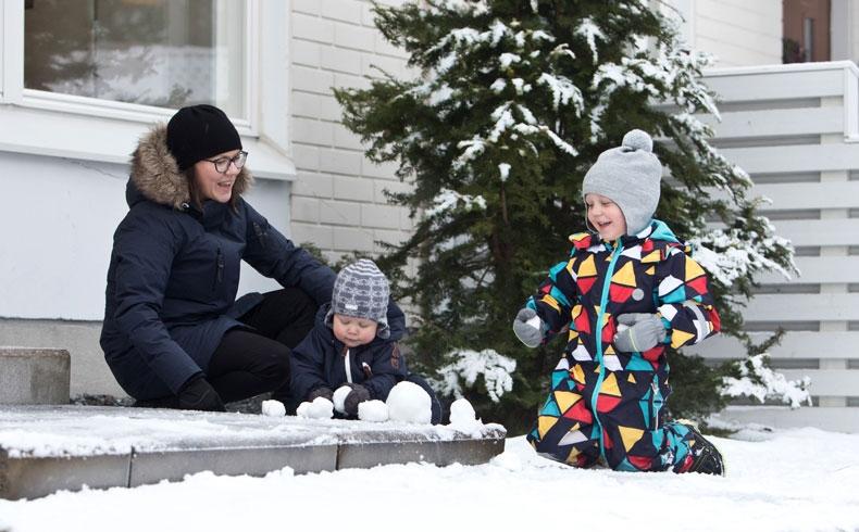 Sabina poikiensa kanssa leikkimässä ulkona lumessa.
