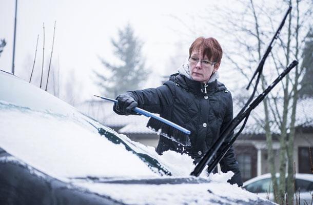 Tuija Jokilaakso puhdistaa auton tuulilasia lumesta.