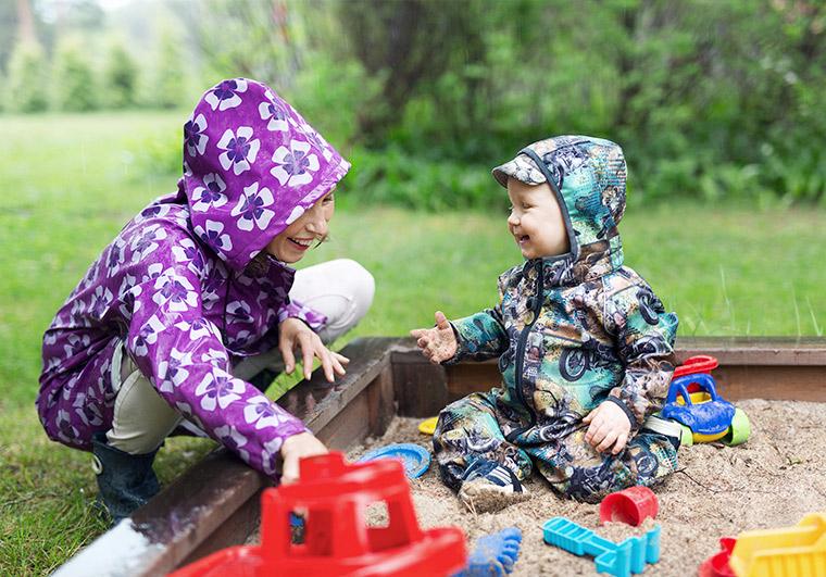 Äiti ja lapsi heikkalaatikolla sadevaatteet päällä.