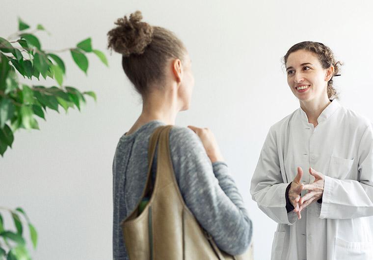 Nainen juttelee lääkärin kanssa.