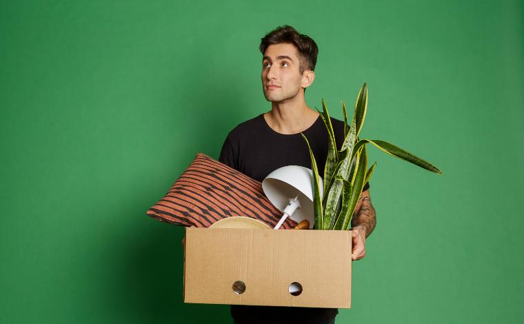 Nuori mies kantaa muuttolaatikkoa.