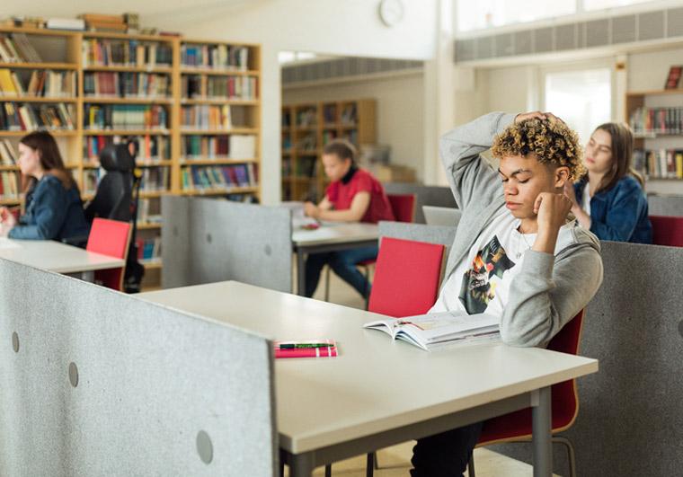 Nuoria opiskelijoita kirjastossa lukemassa.