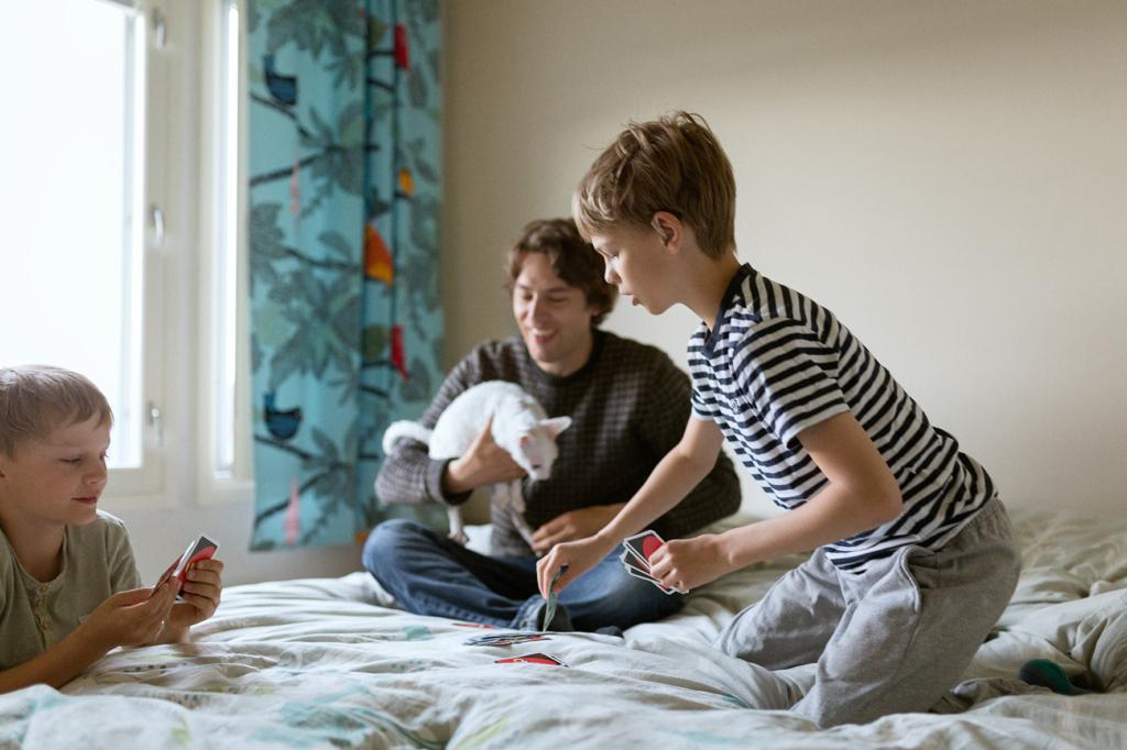 Isä ja pojat pelaa Uno-peliä sängyllä.