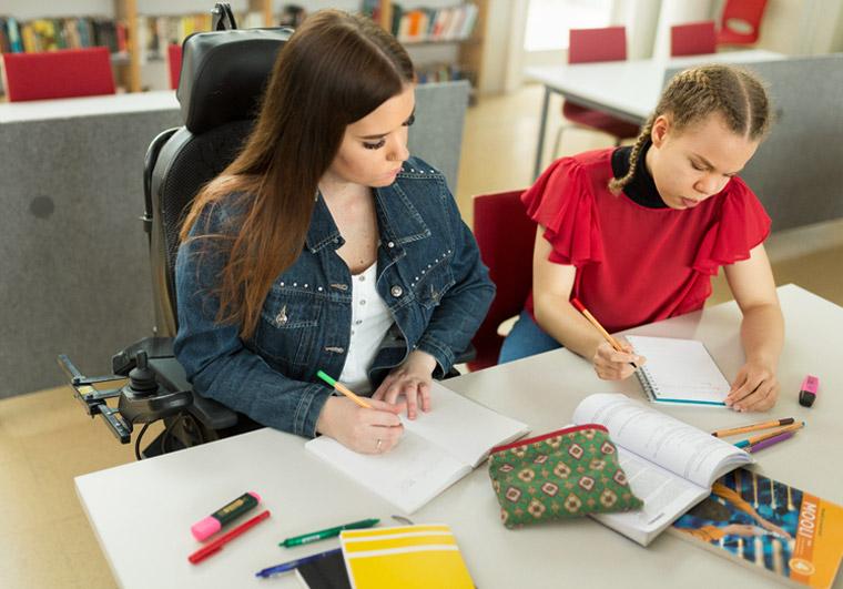 Pyörätuolissa istuva opiskelijatyttö kaverinsa kanssa tekemässä läksyjä.