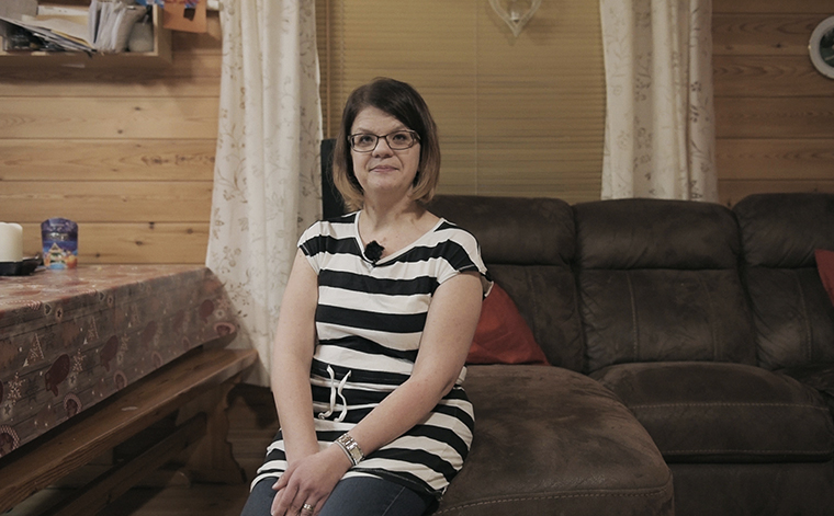 Anne Markkanen istuu kotonaan sohvalla.