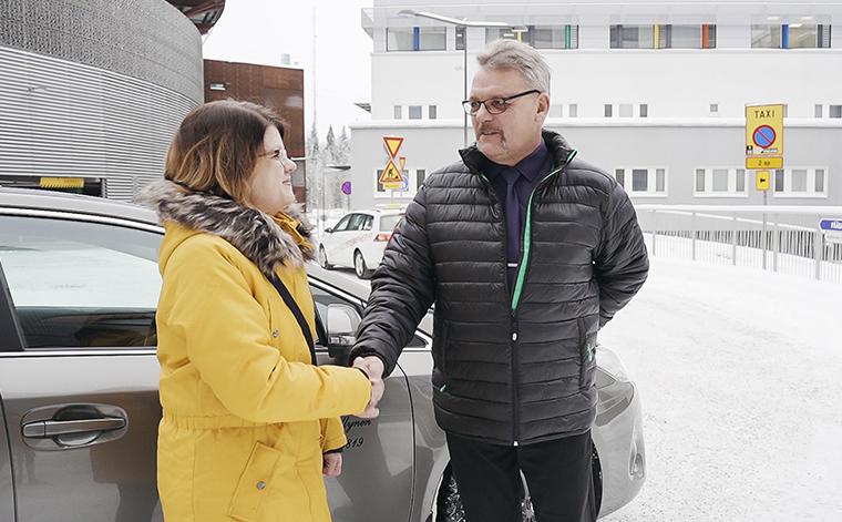 Anne Markkanen ja taksinkuljettaja Veli Myllynen kättelevät sairaalan pihalla.
