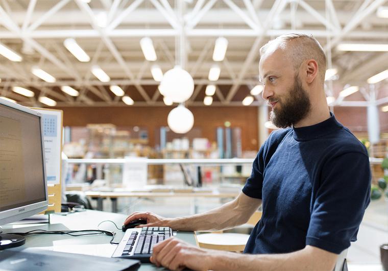 Mies tietokoneella.