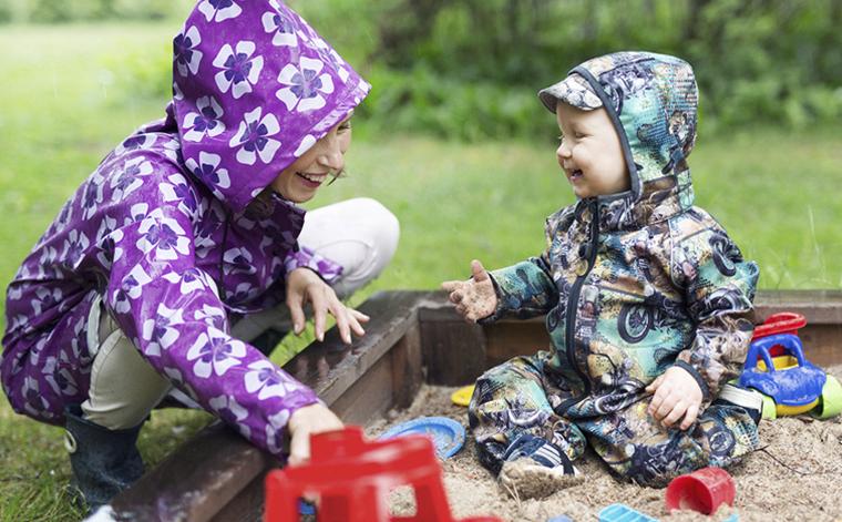 Moder och barn i en sandlåda med regnkläder på.