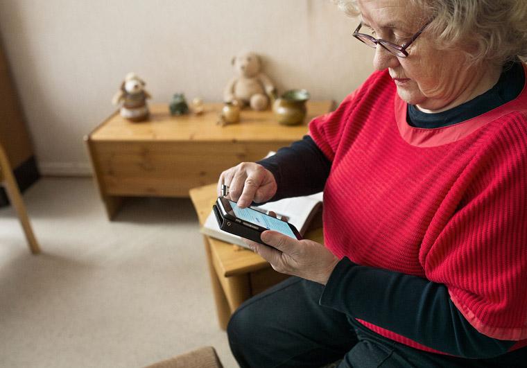 Eläkeläinen käyttää älypuhelinta.