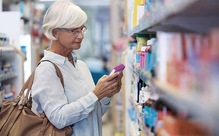 nainen katselee tuotteita apteekissa