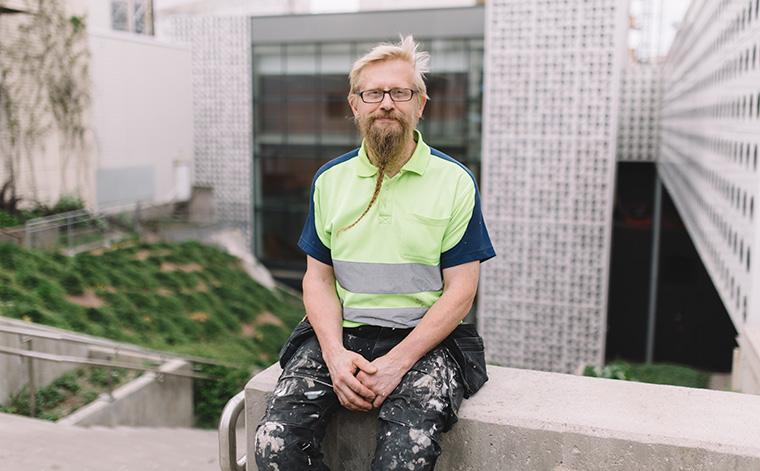 Jouko Vidgren istuu ulkona työvaatteissaan.