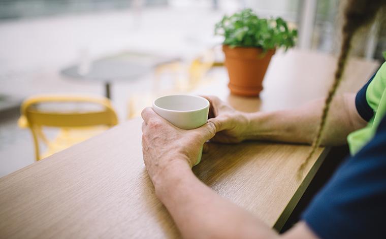 Kahvikuppia pitelevät kädet ja pitkä letitetty parta.