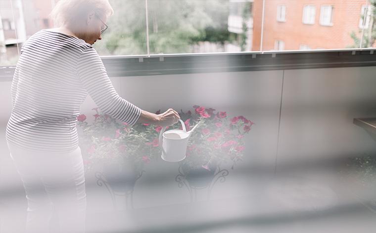 Marja kastelee kukkia parvekkeella.