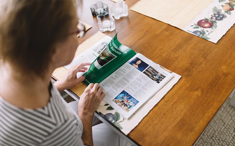 Marja selaa lehteä.
