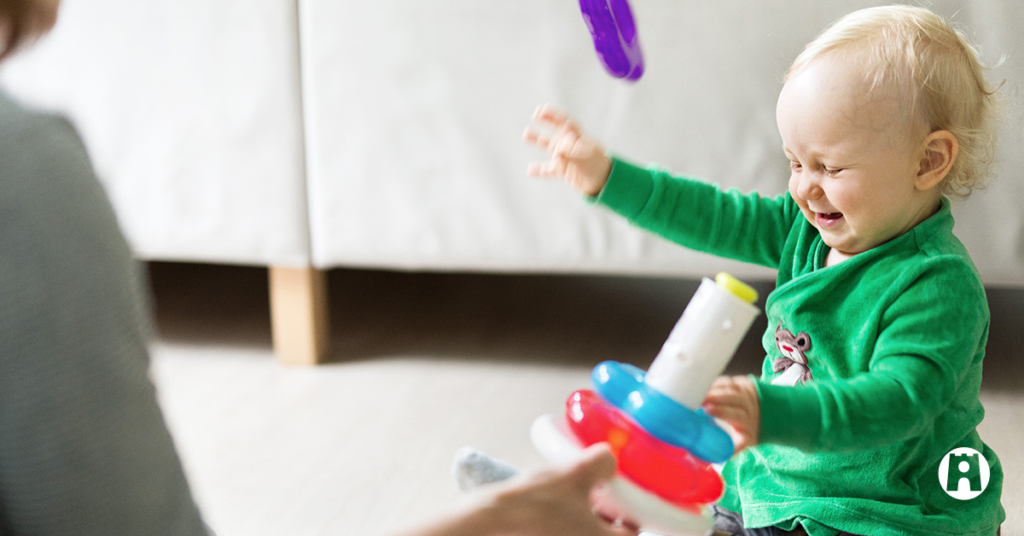 Kuvituskuva. Pieni lapsi nauraa ja leikkii innoissaan.