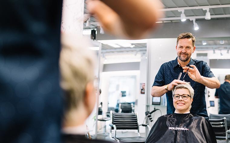 Jukka Lautamaja kampaa asiakkaan hiuksia.