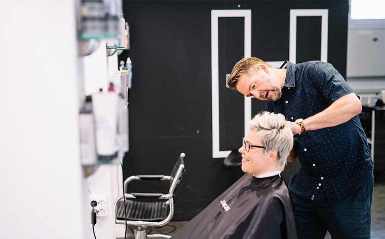 Jukka Lautamaja leikkaa asiakkaan hiuksia.