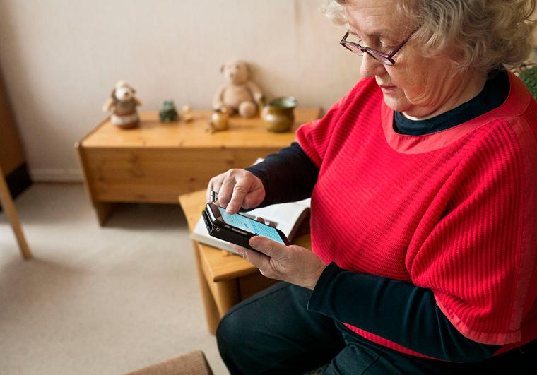 Kuvituskuva. Iäkäs nainen käyttää älypuhelinta.