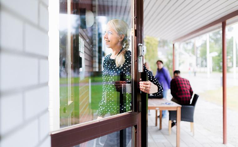 Sari Paananen astuu koulun ovesta sisään.