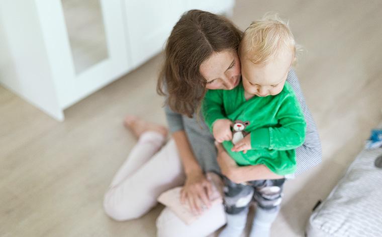 Kuvituskuva. Äiti halaa pientä lastaan.