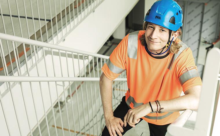 Nuori rakennusmies kiipeää portaita. ylös.