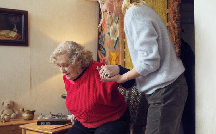 Kuvituskuva. Tyttö auttaa mummoa nousemaan tuolista.