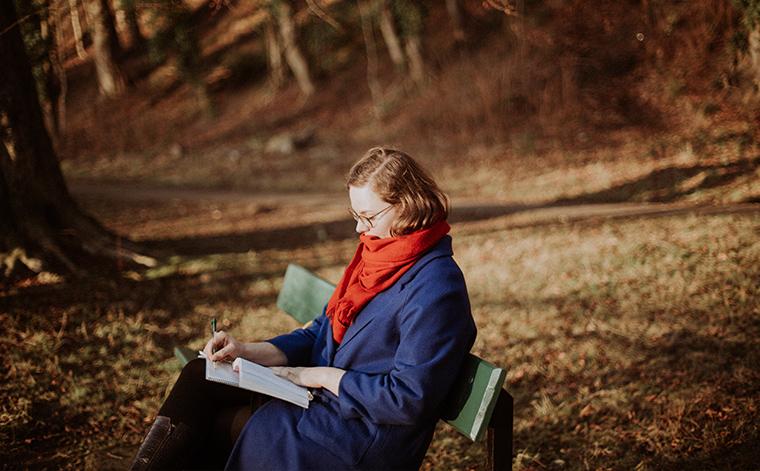 Sofia Savonen lukee puistonpenkillä.