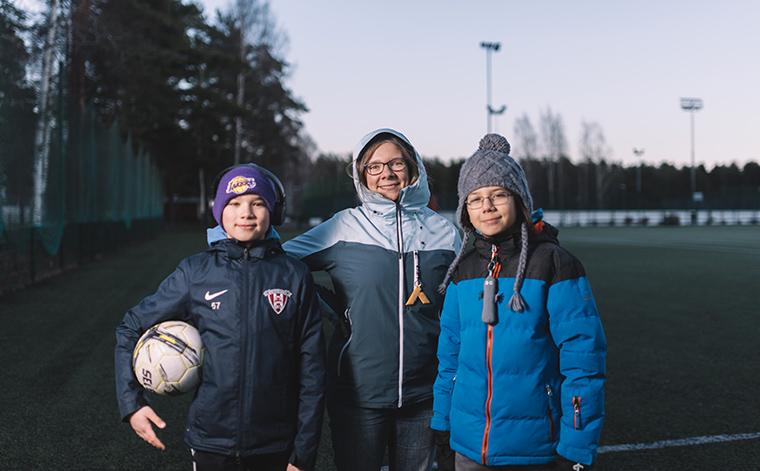 Samuel, Riina ja Benjamin Nguyen jalkapallokentän laidalla.
