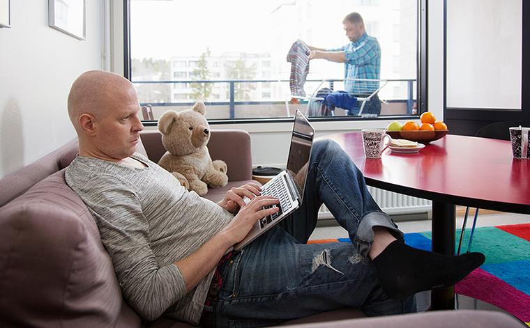 Kuvituskuva. Mies sohvalla katsoo tietokonetta.