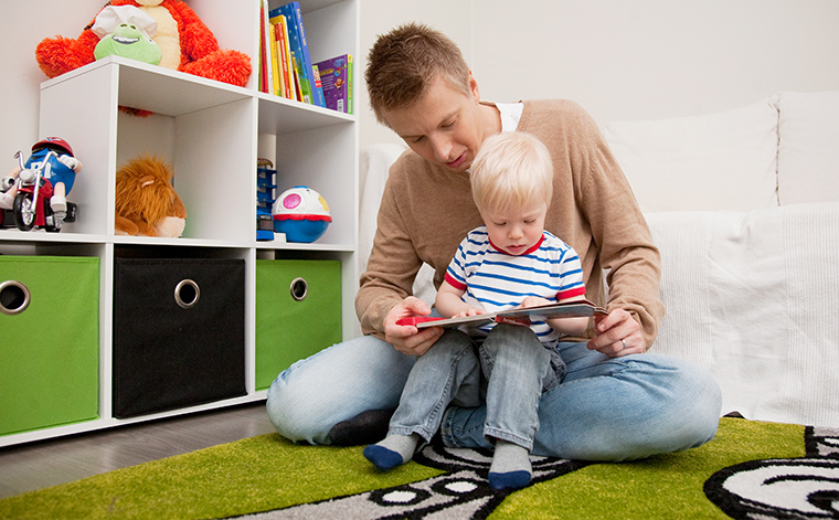 Kuvituskuva. Mies lukee kirjaa pienen lapsen kanssa.