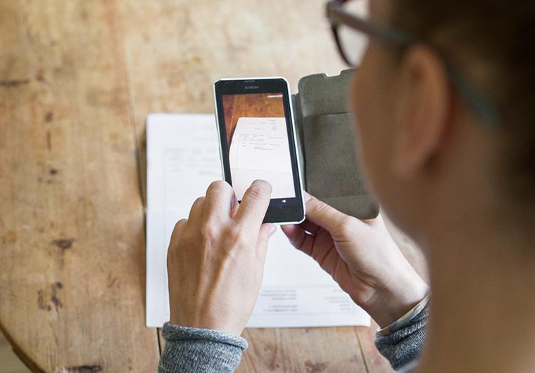 Kuvituskuva. Nainen ottaa kännykällä kuvaa liitteestä.