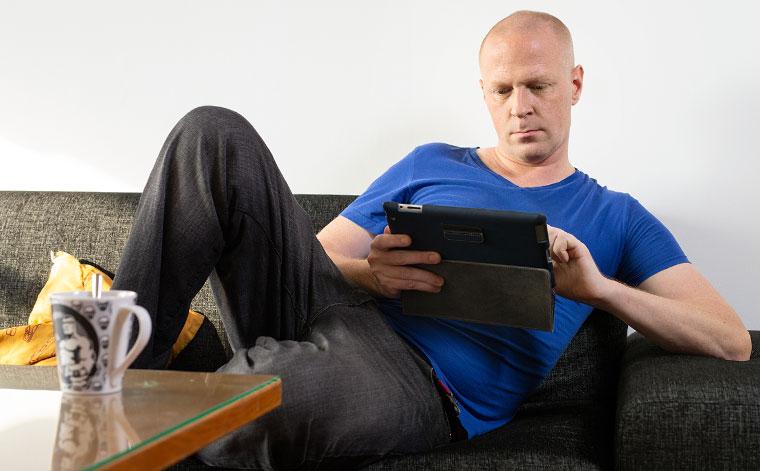 Mies istuu sohvalla ja lukee tablettia.