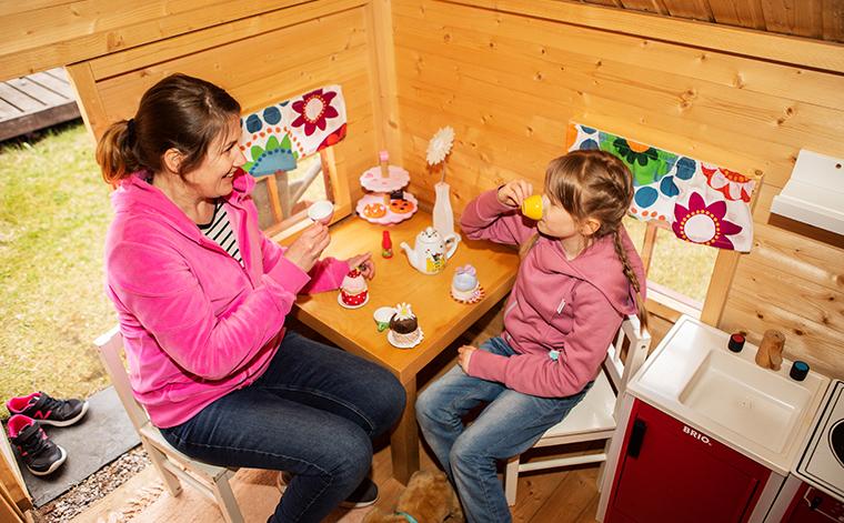 Kirsi Somervuo ja tytär kahvittelevat leikkimökissä.