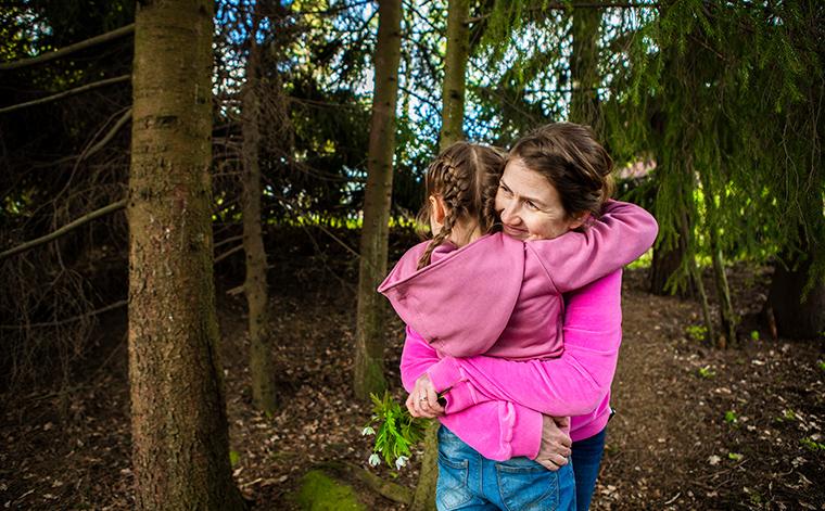 Kirsi Somervuo halaa Violaa metsässä.