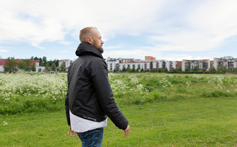 Mies kävelee ulkona. Taustalla vihreää ja asuinalue.