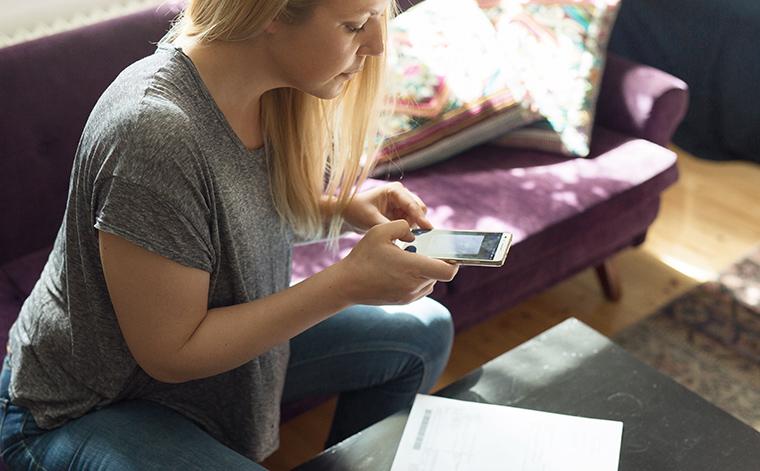 Nainen kuvaa puhelimella lomaketta.