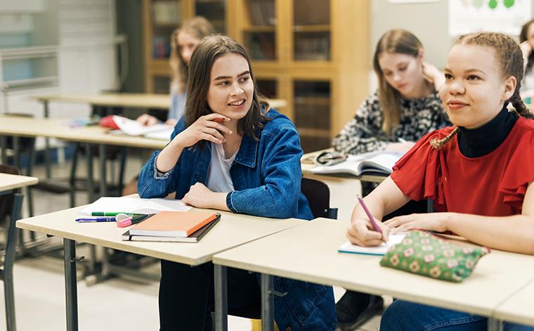 Kaksi opiskelijaa pulpettien ääressä.