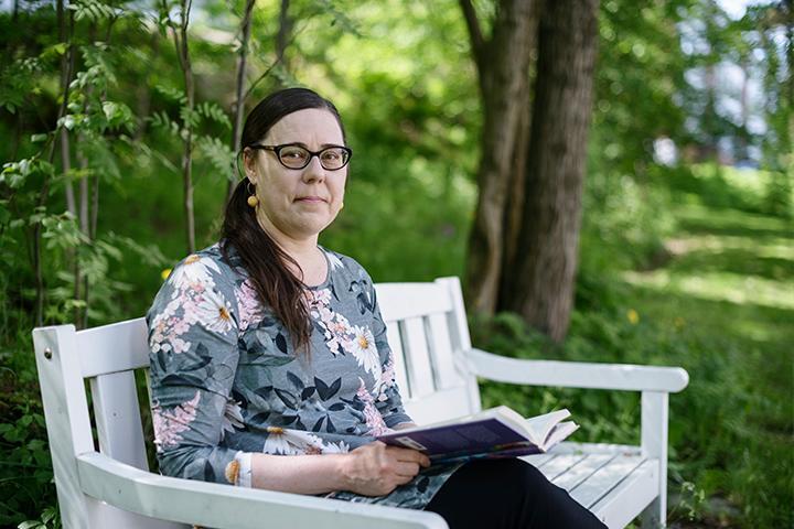 Katja Jokiniemi istuu puistonpenkillä kirja sylissä ja katsoo kameraan.