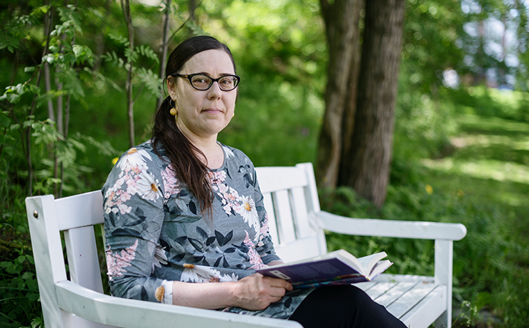 Katja Jokiniemi sitter på en parkbänk med en bok i famnen och tittar in i kameran.