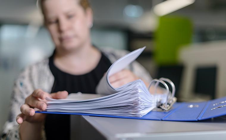Tiina Raitanen bläddrar bland pappren i en mapp.