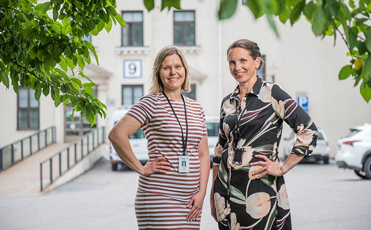 Elina Alm ja Jaana Häyrinen seisovat ulkona sairaalan edessä hymyillen kameraan.