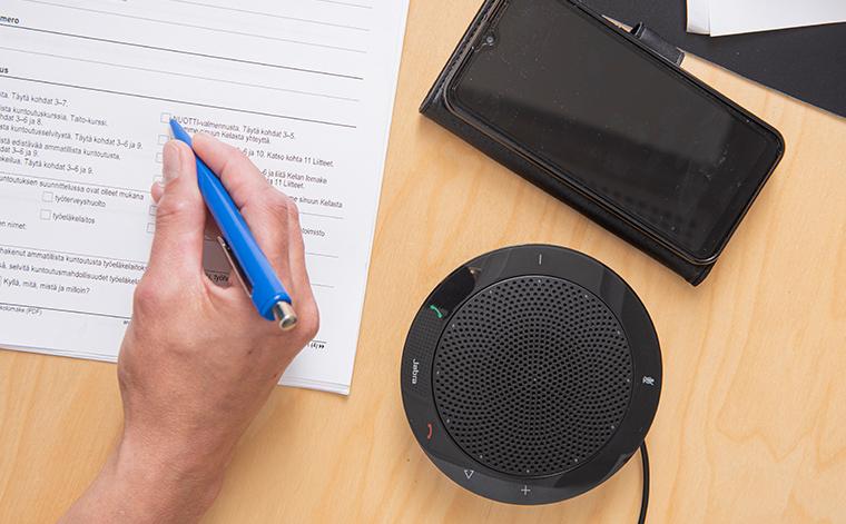 En hand håller pennan ovanför blanketten, intill på bordet ligger ett telefonfodral och en högtalare.
