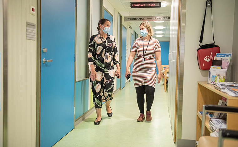 Jaana Häyrinen och Elina Alm går i en sjukhuskorridor med ansiktsmasker på och ser på varandra.