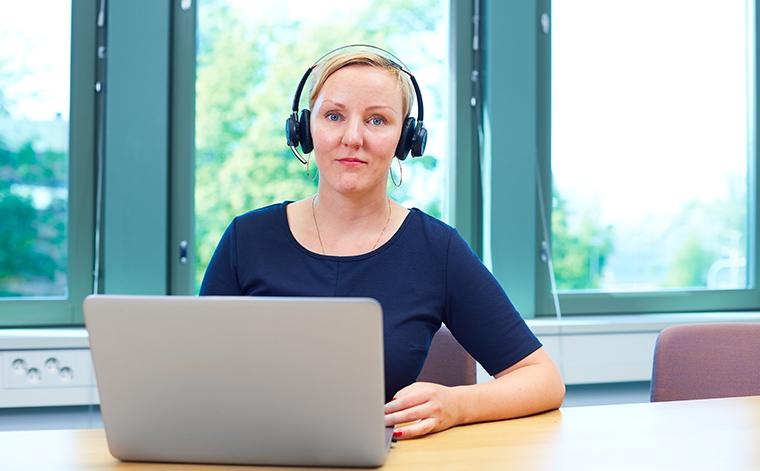Mira Matikka vid datorn med headset på huvudet.